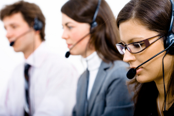 Customer service team working in headsets, woman in front.